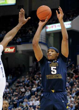 West Virginia's Kevin Jones (5) takes a 3-pointer during the first half of an NCAA college basketball game against Connecticut in Hartford, Conn., on Monday, Jan. 9, 2012. (AP Photo/Fred Beckham) Photo: Fred Beckham, Associated Press / FR153656 AP