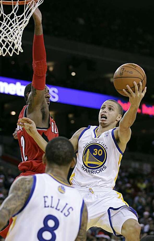 Golden State Warriors guard Stephen Curry (30) drives to the basket against Portland Trail Blazers forward LaMarcus Aldridge, left, as Warriors guard Monta Ellis (8) looks on during the second half of an NBA basketball game in Oakland, Calif., Saturday, Dec. 25, 2010. Warriors won 109-102. Photo: Tony Avelar, AP