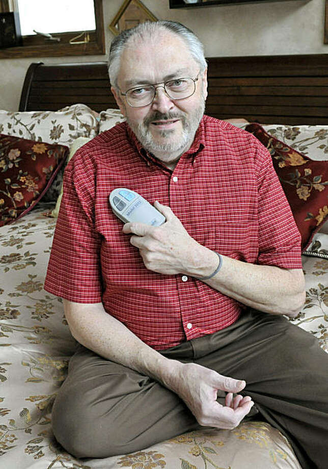 Rik Krohn displays the remote control unit he uses to turn on an experimental nerve stimulator to combat his sleep apnea, Tuesday, Dec. 21, 2010, at his home in Burnsville, Minn. Loud snoring may do more than irritate your spouse: It can signal sleep apnea, depriving you of enough zzzz's to trigger a car crash, even a heart attack. Now scientists are testing if an implanted device might help, keeping sufferers' airways open by zapping the tongue during sleep. Photo: Jim Mone, AP
