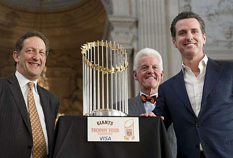 San Francisco Giants President Larry Baer, owner Bill Neukom, and San Francisco Mayor Gavin Newsom, from left, huddle around the World series champion Commissioner's Trophy for a photo at the announcement of the start of the trophy tour on Wednesday, Dec. 15, 2010, at San Francisco City Hall. The tour will begin on Jan. 4, 2011.(Adam Lau/Special to The Chronicle) Photo: Adam Lau, Special To The Chronicle