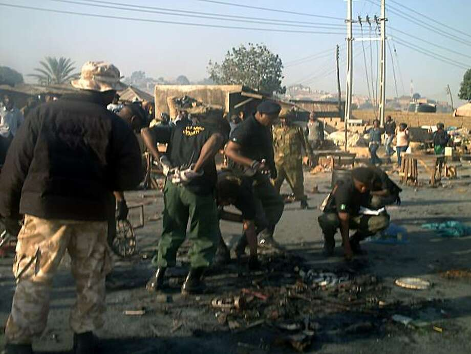 A team of military and police bomb squad pick pieces of detonated explosives on December 24, 2010 in Jos where multiple explosions in some parts of the city on Christmas eve killed 32 and injured 74. A series of bombings in central Nigeria ahead of Aprilelections has added a frightening new dimension to an already deadly power struggle in the region opposing Christian and Muslim ethnic groups. Photo: Aminu Abubakar, AFP/Getty Images