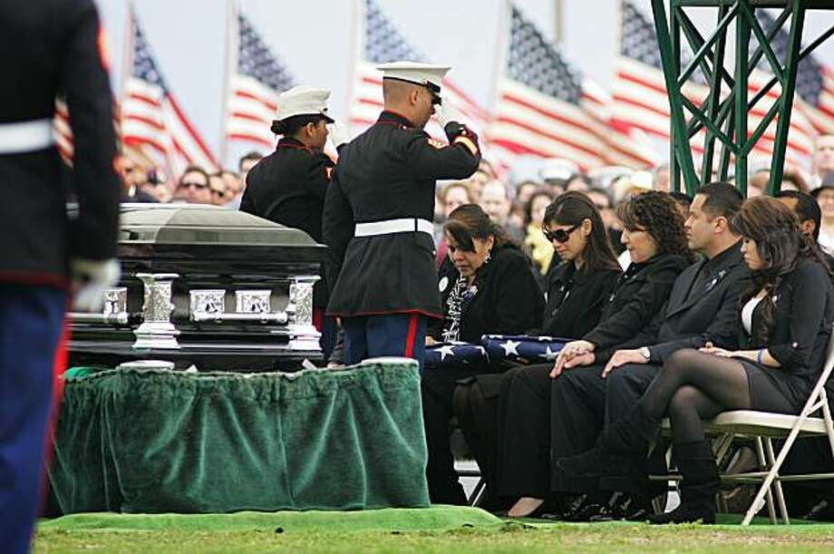 In this March 8, 2010 file photo, Marines salute Saloma Bejar and Mariam Bejar, the mother and wife of fallen officer Javier Bejar, after presenting the ceremonial flag at cemetery services in Reedley, Calif. Cluster killings of more than one officer helped make 2010 a particularly dangerous year for police officers. Some 160 officers died in the line of duty, a 37 percent jump from the same period in 2009 when 117 officers were killed, according to statistics compiled by the National Law Enforcement Officers Memorial Fund, a nonprofit that tracks police deaths. Photo: Gary Kazanjian, AP