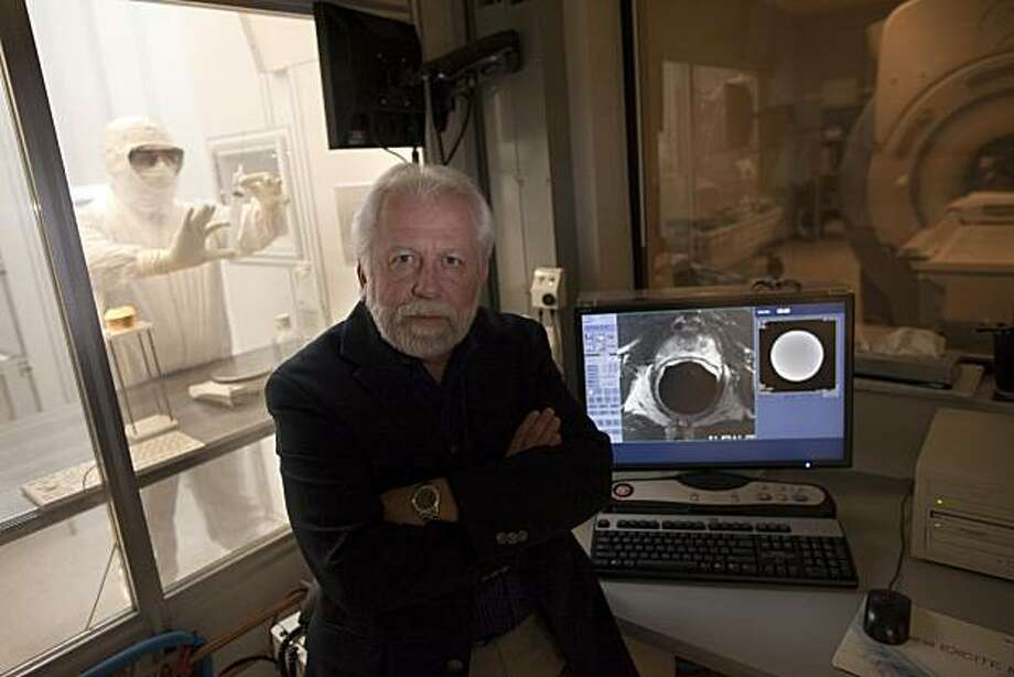 John Kurhanewicz, Ph.D of Radiology and Bio Medical Imaging poses for a photograph along side a computer monitor of a 66 year old prostate as Jose (Pepe) Rodriguez, pharmacy technician works in the clean room of the UCSF Mission Bay Campus on December 20, 2010 in San Francisco, Calif.  Photograph by David Paul Morris/Special to the Chronicle Photo: David Paul Morris, Special To The Chronicle