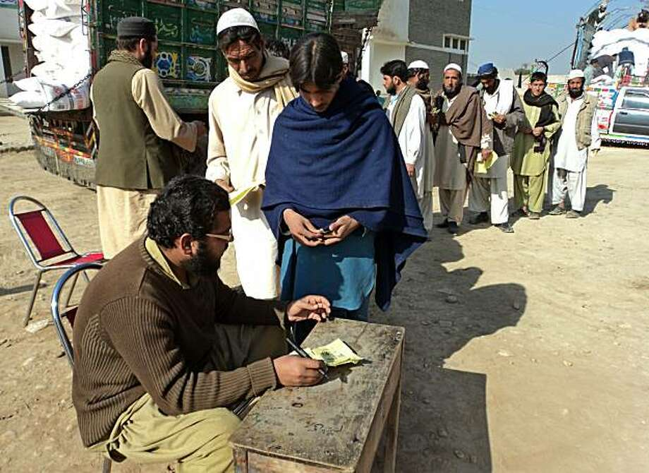 A Pakistani employee registers internally displaced persons (IDPs) at the World Food Programme distribution point in Tank on December 26, 2010. More than 80 people were killed in a suicide bombing on a World Food Programme project and a series of helicopter raids against militant camps in northwestern Pakistan, officials said. Photo: Rafi Burki, AFP/Getty Images