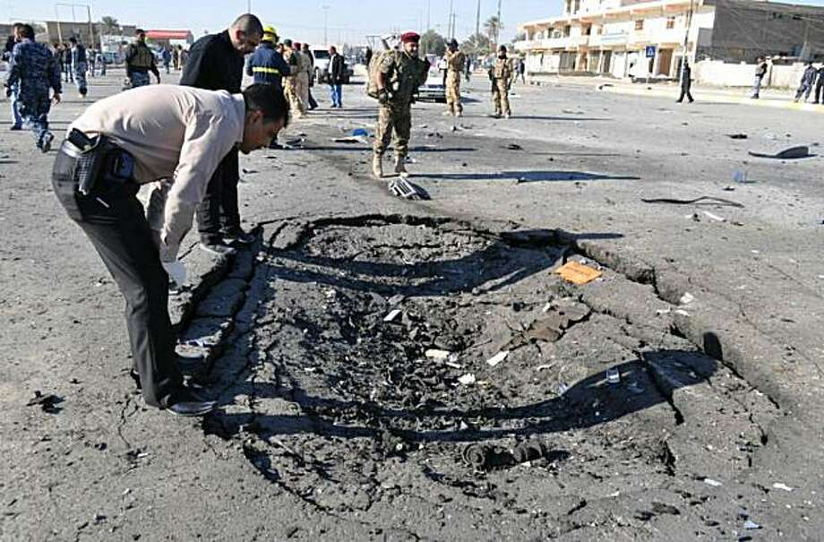A plain clothed police officer inspects the scene following a car bomb and minutes later a suicide bombing targeting the provincial headquarters in the western Iraqi city of Ramadi, killing a number of people, including policemen, and injuring scores of others on December 27, 2010, according to the police. Photo: Azhar Shallal, AFP/Getty Images