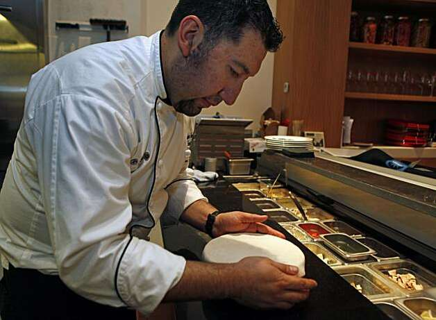 Chef, Gustavo Romero, covers Credo signature dish Sedanini all Credo, with pizza dough. The dish is made up of sausage; pasta and a sauce of Sage, Garlic and peppers toped with the dough and baked in the pizza oven at 528 degrees. Wednesday Dec 12, 2010 Photo: Lance Iversen, The Chronicle