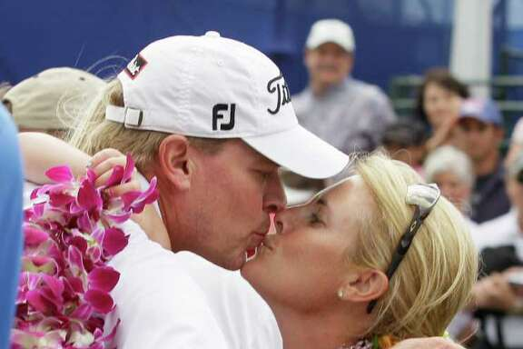 Steve Stricker is embraced by his wife, Nicki, after winning the Hyundai Tournament of Champions PGA Tour golf tournament in Kapalua, Hawaii, Monday, Jan. 9, 2012. Stricker shot a 4-under-par 69, winning by three shots.