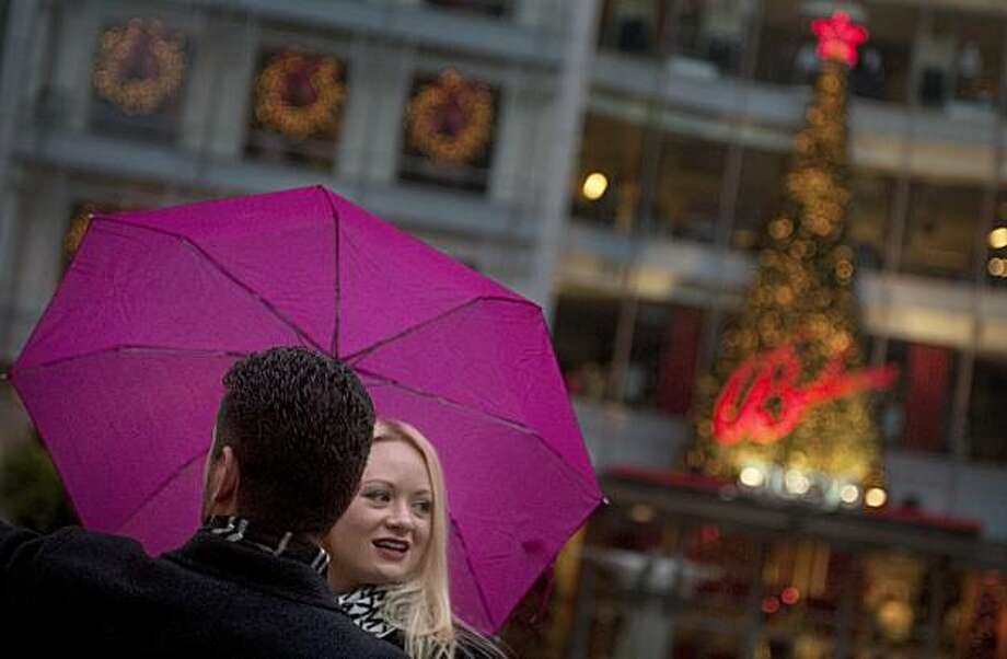Monique Katchor and Michael Imbriani of San Francisco, from right, stay dry while walking through Union Square on Christmas Day, Saturday, Dec. 25, 2010, in San Francisco, Calif. (Adam Lau/Special to The Chronicle) Photo: Adam Lau, Special To The Chronicle
