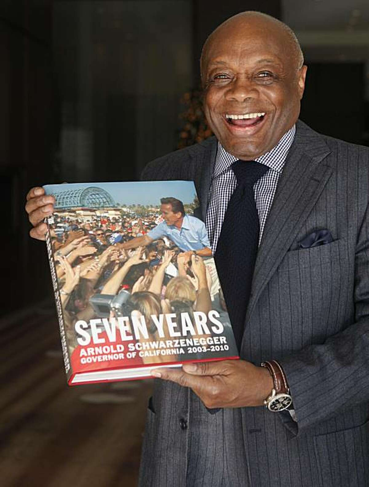 Standing in the lobby of the St. Regis Hotel, Former San Francisco Mayor Willie Brown holds a copy of a limited run picture book that makes light of Governor Arnold Schwerzenegger's 7 year term on Wednesday Dec. 8, 2010 in San Francisco, Calif.