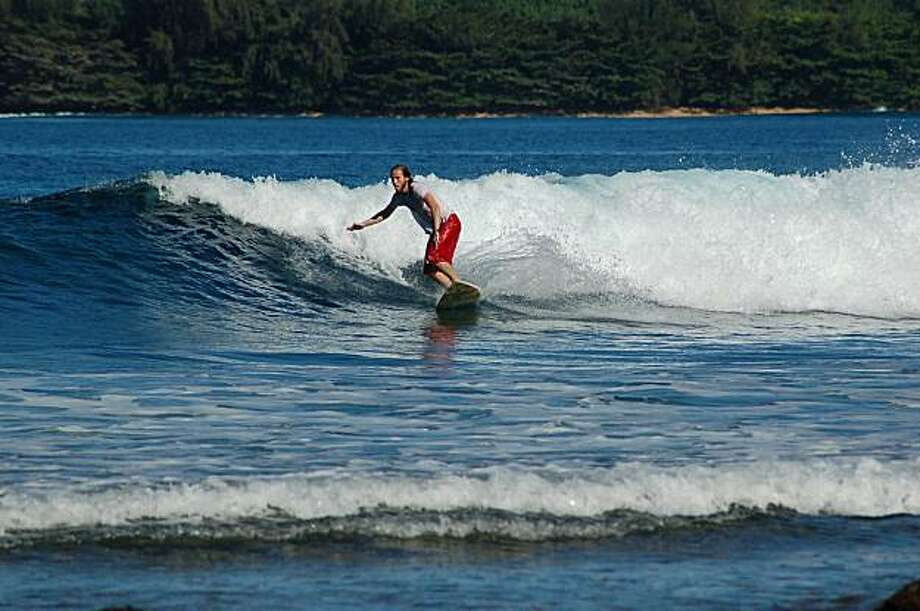 A surfer catches a wave at Hanalei Bay on Kaua'i, site of the first survey conducted by Reef Check. Photo: Jeanne Cooper, Special To SFGate