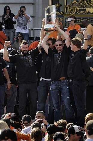 San Francisco Giants' Brian Wilson (l to r), Pat Burrell, Aubrey Huff and Matt Cain hold the 2010 World Series Championship trophy over their heads at the end of  the ceremony at Civic Center Plaza after the World Series parade celebrating the San Francisco Giants win in the 2010 World Series on Monday, November 3, 2010 in San Francisco, Calif. Photo: Lea Suzuki, San Francisco Chronicle