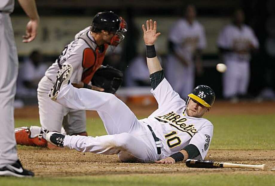 Oakland Athletics' Daric Barton, right, slides safely into home plate to score the A's first run as Boston Red Sox catcher Jarrod Saltalamacchia, left, waits for the throw during the seventh inning of their baseball game in Oakland, Calif., Saturday, Sept. 11, 2010. Barton scored on a double hit by the Athletics' Jack Cust. Photo: Eric Risberg, AP