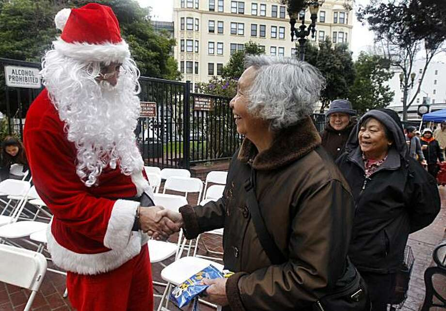 Dressed as Santa Claus, Brian Swartz welcomes Tenderloin residents to a Christmas Day celebration at Boeddeker Park in San Francisco, Calif., on Saturday, Dec. 25, 2010. The San Francisco City Impact Christian Ministry distributed hundreds of meals and toys to neighbors for the 28th straight year. Photo: Paul Chinn, The Chronicle