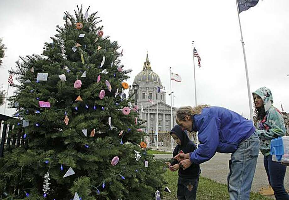"Wayne Standerwick, center, helps three-year-old George Vanuelos, left, place an ornament on the Children's Community Tree as his sister Laura, right, looks on outside City Hall in San Francisco, Tuesday, Dec. 14, 2010. The tree is a project Standerwick started five years ago to teach local schoolchildren the ""joy of giving.""  Each year he buys a small Christmas tree, gets local school kids to design ornaments, and then invites them to decorate it. He calls it a community Christmas tree. To Standwerwick, the tree isn't just a holiday decoration, it's the cornerstone of a global connection. He gets children as far away as Germany and Austria to contribute ornaments and homemade cards. Photo: Byline Withheld, Associated Press"