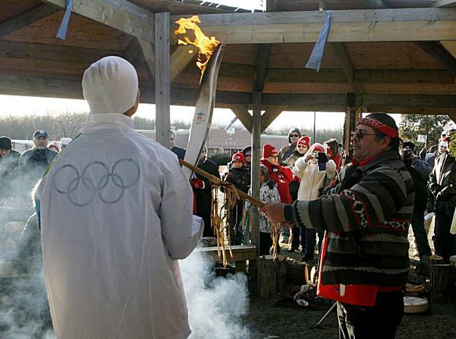 The Vancouver 2010 Olympic torch is held by Monty II McGahey during a ceremony as elder Myeengun blesses the torch and runners at the Chippewas On The Thames, First Nations, in Muncey, Ontario, Canada, Tuesday, Dec. 22, 2009. The torch is making its way west in time for the February opening of the Vancouver Games. (AP Photo/The Canadian Press, Dave Chidley) Photo: Dave Chidley, AP