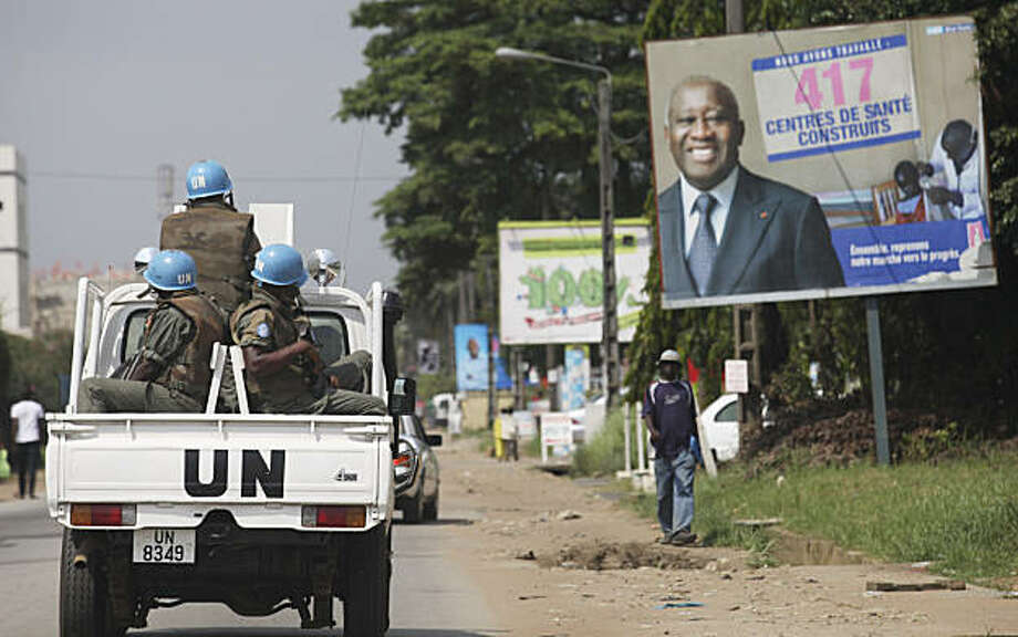UN forces drive past a billboard for President Laurent Gbagbo in, Ivory Coast, Abidjan Thursday, Dec. 23, 2010. The United Nations said Thursday that at least 173 people have been killed and dozens of others have gone missing or been tortured following Ivory Coast's disputed presidential election, which has prompted fears of a return to civil war. Photo: Sunday Alamba, AP