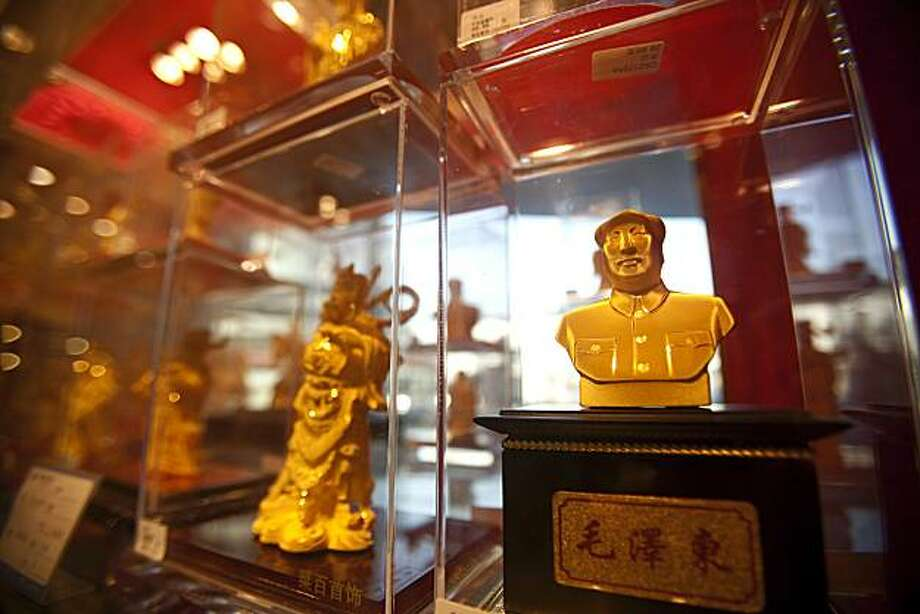 A gold figurine of Mao Zedong, former leader of China, is displayed at Caishikou Department Store in Beijing, China, on Wednesday, Dec. 8, 2010. The rising value of gold -- reaching a record $1,431.25 an ounce on Dec. 7 -- has upended the economics of jewelry forbuyers and sellers alike, with a mix of outcomes around the world. Photographer: Nelson Ching/Bloomberg Photo: Nelson Ching, Bloomberg