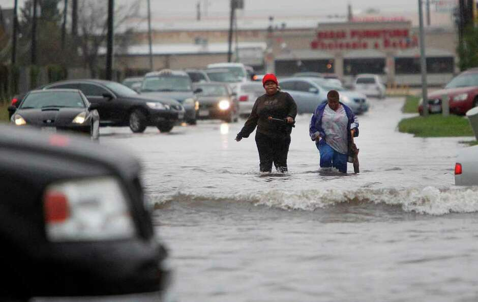 Southwest Houston residents walk through flooded streets as people are trying to get home or to work