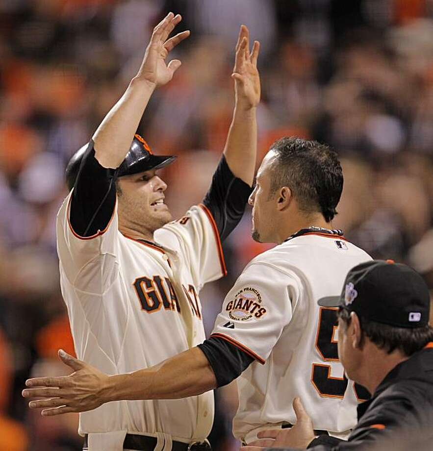 Giants Freddy Sanchez is greeted b Andres Torres after scoring on a Cody Ross single in the fifth inning as the San Francisco Giants take on the Texas Rangers in Game 1 of the World Series at AT&T Park in San Francisco, Calif., on Wednesday, October 27, 2010. Photo: Michael Macor, San Francisco Chronicle
