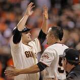 Giants Freddy Sanchez is greeted b Andres Torres after scoring on a Cody Ross single in the fifth inning as the San Francisco Giants take on the Texas Rangers in Game 1 of the World Series at AT&T Park in San Francisco, Calif., on Wednesday, October 27, 2010.