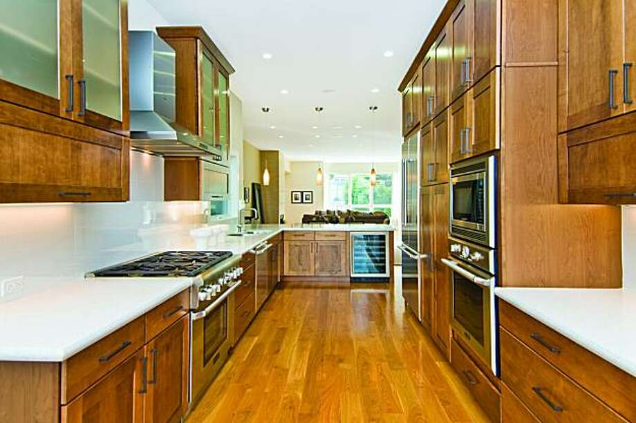 The kitchen has maple cabinetry, Caesarstone countertops, stainless steel appliances including a Thermador refrigerator and range wood, as well as a wall-mounted oven. Photo: Olga Soboleva, Vanguard Properties
