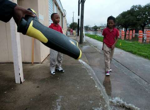 Howard Griggs pours water from his boot after carrying his children, Howard Griggs, Jr., left, and Faith Griggs, from Peck Elementary School following a heavy rain storm that dropped several inches of water throughout the area Monday, Jan. 9, 2012, in Houston. The school was surrounded by floodwaters. Photo: Brett Coomer, Houston Chronicle / © 2012 Houston Chronicle