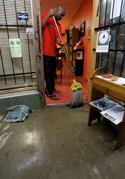 Dr. Perry Kyles mops water from the Khepera Books and African Art store that had floodwaters creep inside following a heavy rain storm that dropped several inches of water throughout the area Monday, Jan. 9, 2012, in Houston. Photo: Brett Coomer, Houston Chronicle / © 2012 Houston Chronicle