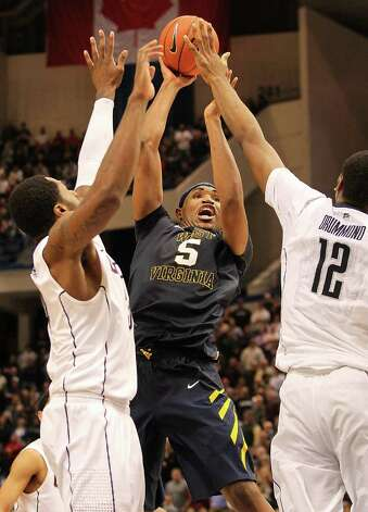 HARTFORD, CT - JANUARY 9: Kevin Jones #5 of the West Virginia Mountaineers feels the pressure from Andre Drummond #12 and Alex Oriakhi #34 of the Connecticut Huskies in the second half at the XL Center on January 9, 2012 in Hartford, Connecticut.  (Photo by Jim Rogash/Getty Images) Photo: Jim Rogash, Getty Images / 2012 Getty Images