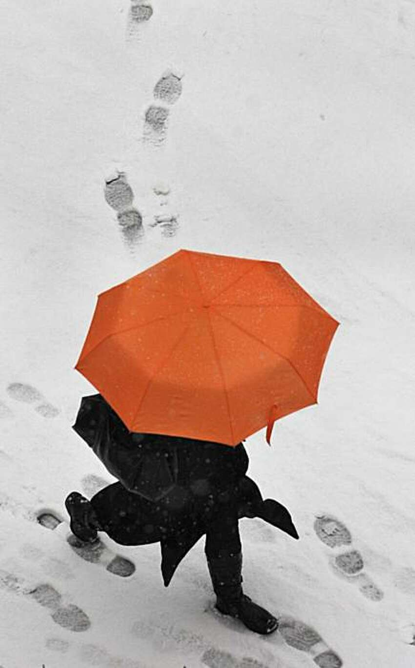 A man with umbrella walks on a snow covered street in Dresden, Germany, Wednesday.