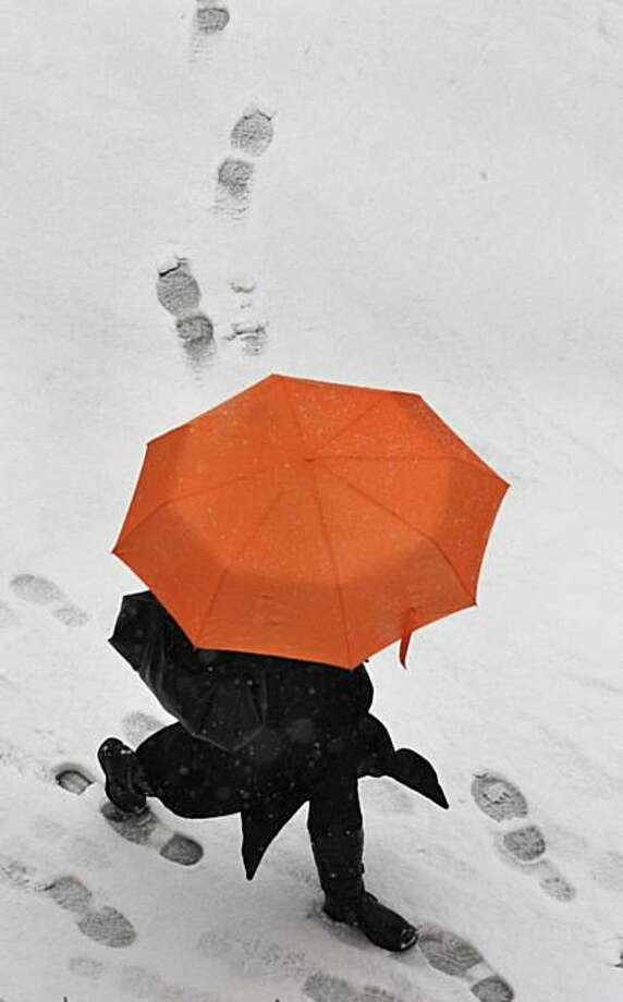 A man with umbrella walks on a snow covered street in Dresden, Germany, Wednesday. Photo: Matthias Rietschel, AP