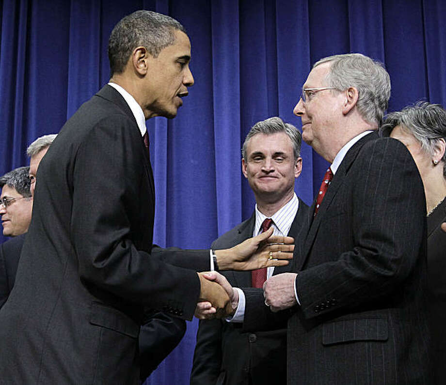 President Barack Obama, left, shakes hands with Senate Republican Leader Mitch McConnell, R-Ky., right, after signing the $858 billion tax deal into law in a ceremony in the Eisenhower Executive Office Building on the White House complex, Friday, Dec. 17,2010 in Washington. Photo: Pablo Martinez Monsivais, AP