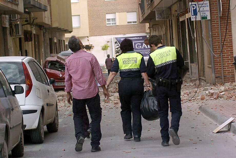 A man looks up as he walks down the street with two Police officers after an earthquake hit the southern Spanish village of Lorca, Wednesday May 11, 2011. Two earthquakes struck southeast Spain in quick succession Wednesday, killing several people, and injuring dozens and causing major damage to buildings, officials said. The epicenter of the quakes with magnitudes of 4.4 and 5.2  was close to the town of Lorca, and the second came about two hours after the first. Photo: Israel Sanchez, AP