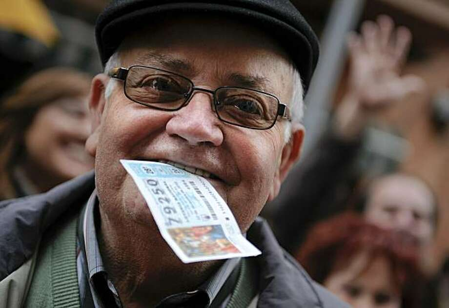 BARCELONA, SPAIN - DECEMBER 22:  A winner of 'El Gordo' bites his winning ticket at the bar which sold the largest amount of winning tickets for the spanish lottery on December 22, 2010 in Barcelona, Spain. This year's prize pot for Spain's traditional Christmas lottery 'El Gordo' rose to 2.3 billion euros, with winners holding tickets numbered 79250 receiving a first prize of 300,000 euros. Photo: David Ramos, Getty Images