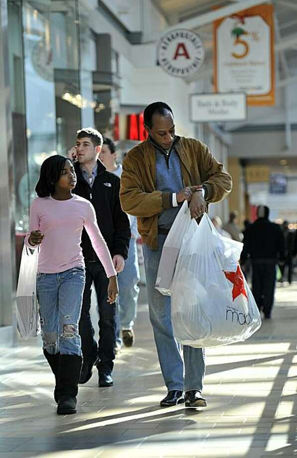 BRIDGEWATER TWP, NJ- DECEMBER 24:  Last minute Christmas shoppers Larry McRae and his daughter Lauren (age 9) of Far Hills, NJ carry bags of merchandise through Bridgewater Commons Mall December 24, 2010 in Bridgewater TWP, New Jersey. On the day of Christmas eve, shoppers brave cold temperatures and gusty winds to take care of last-minute shopping needs. Photo: Matt Rainey, Getty Images