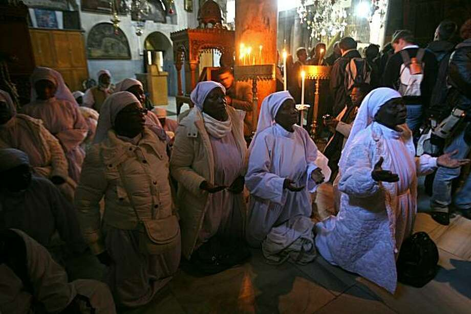 Nigerian Christian pilgrims pray at the Church of the Nativity, believed to be the birthplace of Jesus Christ, in the West Bank town of Bethlehem on December 24, 2010 as the Holy Land prepared to mark Christmas. Photo: Musa Al-shaer, AFP/Getty Images