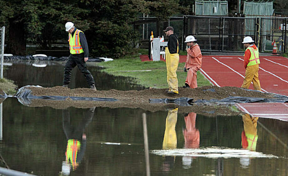 Workers from the Ross Valley Sanitation District view the raw sewage spill behind Kent Middle School in Kentfield, Calif., on Wednesday December 22,  2010. Photo: John Storey, Special To The Chronicle