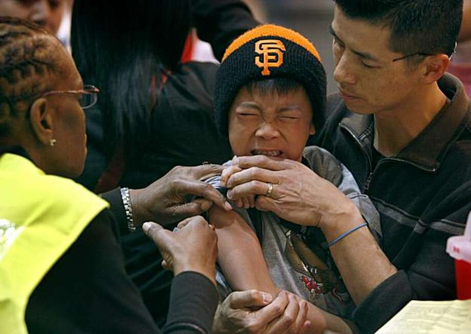 Seven-year-old Ben Ng grits his teeth and is held by his father Eddie Ng as Ivy Steverson (left) vaccinates him against the H1N1 influenza at an all-day innoculation clinic at the Bill Graham Civic Auditorium in San Francisco Tuesday. Photo: Paul Chinn, The Chronicle