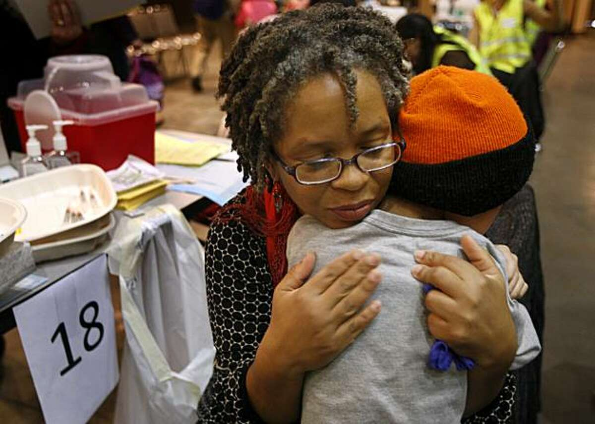 Medical technician Lisa Watson hugs Ben Ng after the 7-year-old received his H1N1 flu vaccination at the Bill Graham Civic Auditorium in San Francisco Tuesday.