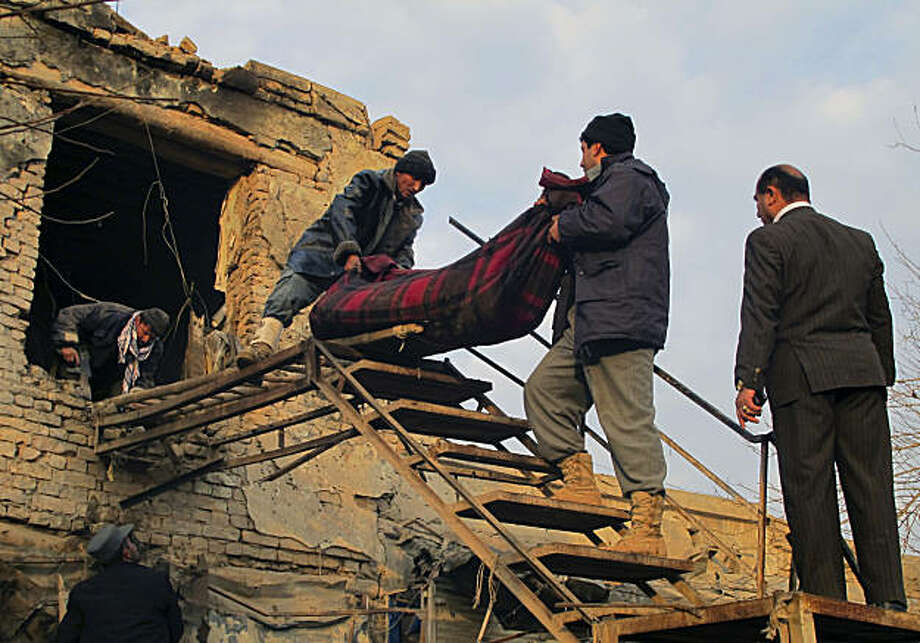 CORRECTS PHOTOGRAPHER'S NAME IN THE MAIN CAPTION BODY -Afghan police men carry a wrapped body of a police officer, who was killed by a suicide attack in Kunduz, north of Kabul, Afghanistan on Thursday, Dec. 23, 2010. Three civilians were also wounded in the blast. The bombing is the second suicide attack in less than a week in Kunduz city. Photo: Fulad Hamdard, AP