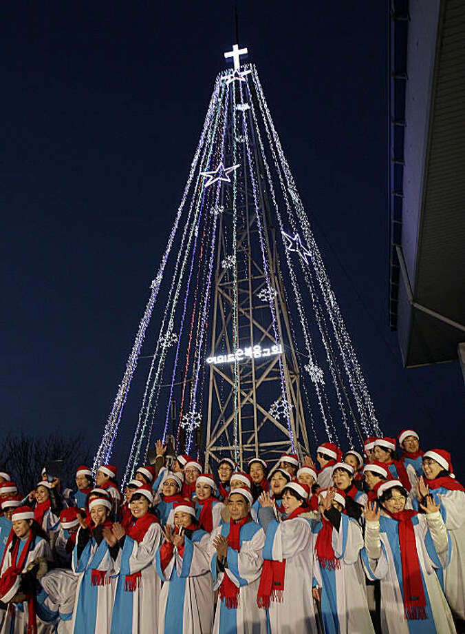 South Korean Christians sing a Christmas song in front of a 100-foot-tall (30-meter-tall) steel Christmas tree that would be visible North Koreans living near the Demilitarized Zone dividing the two Koreas at the western mountain peak known as Aegibong inGimpo, South Korea, Tuesday, Dec. 21, 2010. The Christmas lights went on again for the first time in seven years. Photo: Lee Jin-man, AP