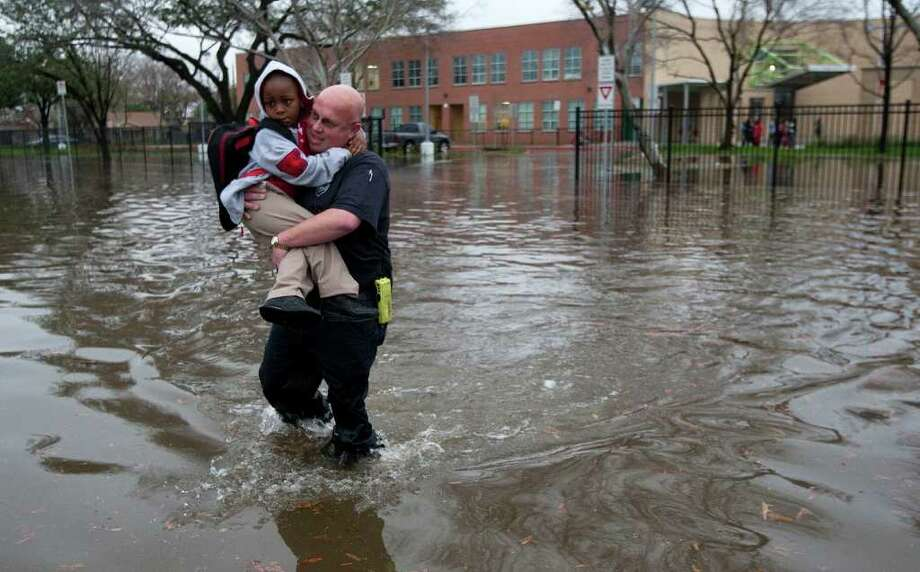 Houston firefighter Scotch Blair carries Dezmund Chapman, 5, through a flooded street next to Peck Elementary in southeast Houston. The school will be closed Tuesday, HISD officials said.  See more photos on Page B1. Photo: Brett Coomer / © 2012 Houston Chronicle