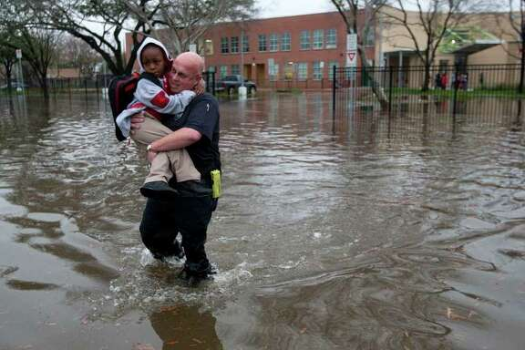 Houston firefighter Scotch Blair carries Dezmund Chapman, 5, through a flooded street next to Peck Elementary in southeast Houston. The school will be closed Tuesday, HISD officials said.  See more photos on Page B1.