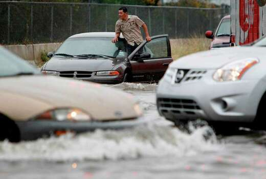 A stranded motorist refuses to abandon his car in the Fondren-Harwin intersection in southwest Houston. Photo: Mayra Beltran / © 2011 Houston Chronicle
