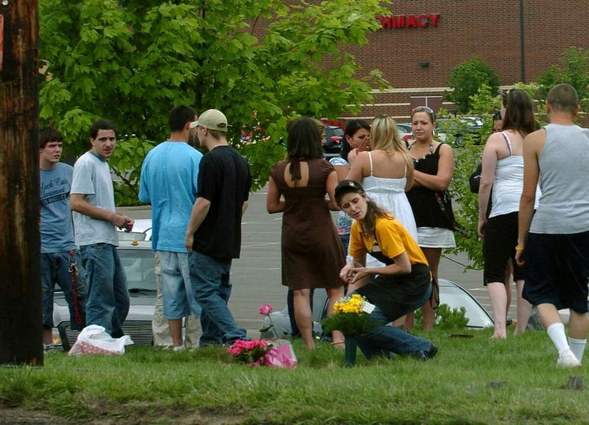 People gather to place flowers and grieve at the scene of a fatal accident which ocurred along Post Road and Dogwood Road in Orange, CT on Saturday June 13, 2009.