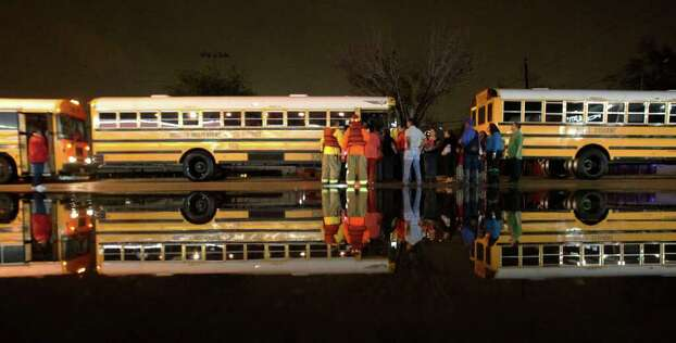 Houston Fire Department personnel stage buses for school students during high water rescues by dump trucks near Griggs Road and Martin Luther King Boulevard Monday, Jan. 9, 2012, in Houston. ( James Nielsen / Chronicle ) Photo: James Nielsen / © 2011 Houston Chronicle