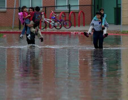 Parents of Peck Elementary School students wade through floodwaters to take their children home after heavy rain flooded the streets around the school Monday, Jan. 9, 2012, in Houston. ( Brett Coomer / Houston Chronicle ) Photo: Brett Coomer / © 2012 Houston Chronicle