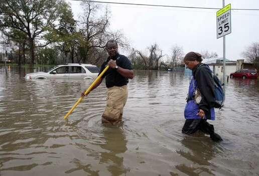 A Houston Fire Department firefighter escorts Dominga Britton right, to her home during high water rescues near Griggs Road and Martin Luther King Boulevard Monday, Jan. 9, 2012, in Houston. ( James Nielsen / Chronicle ) Photo: James Nielsen / © 2011 Houston Chronicle
