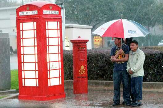 Alex Prayan and Jorge Prayan wait for the Metro bus along Westheimer and Kirby as the storm moves through the Houston area on Monday, Jan. 9, 2012, in Houston. ( Mayra Beltran / Houston Chronicle ) Photo: Mayra Beltran / © 2011 Houston Chronicle