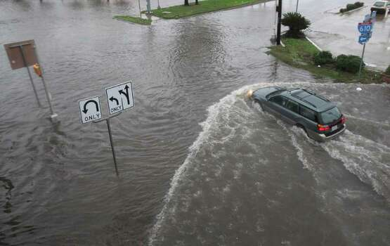 A motorist drives through high water along the feeder road of Southwest Freeway (59) and Stella Link Road as a heavy thunderstorm moves through the Houston area on Monday, Jan. 9, 2012, in Houston. ( Mayra Beltran / Houston Chronicle ) Photo: Mayra Beltran / © 2011 Houston Chronicle