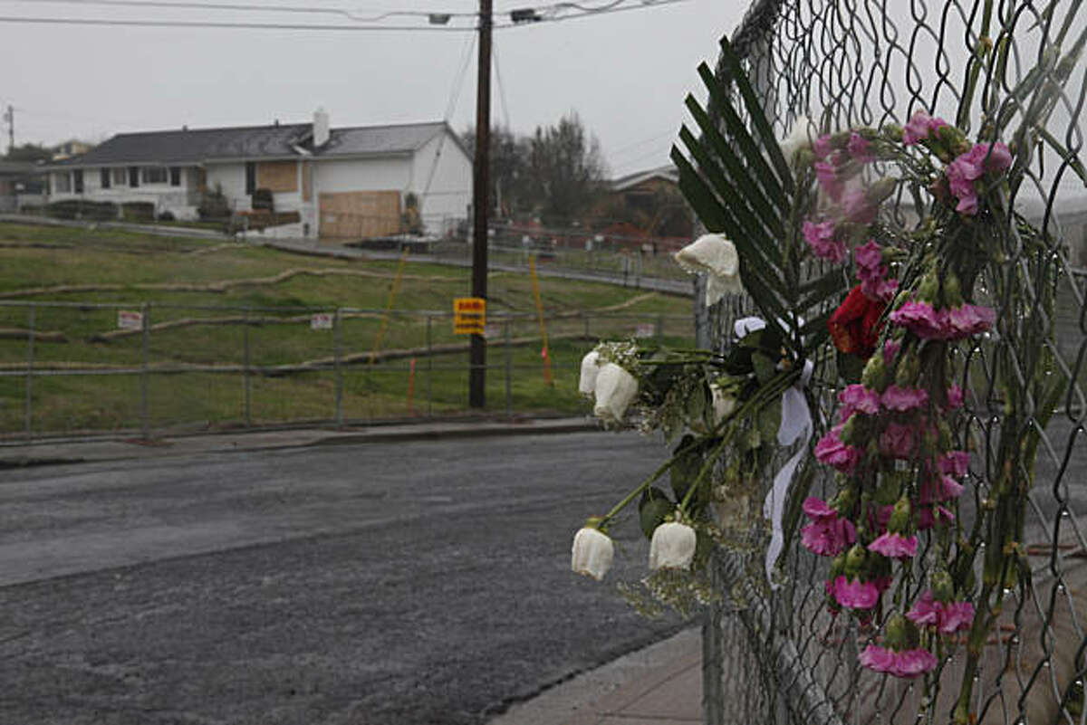 Bouquets of flowers placed on a fence along Claremont Drive are seen on Friday, December 17, 2010 in San Bruno, Calif.